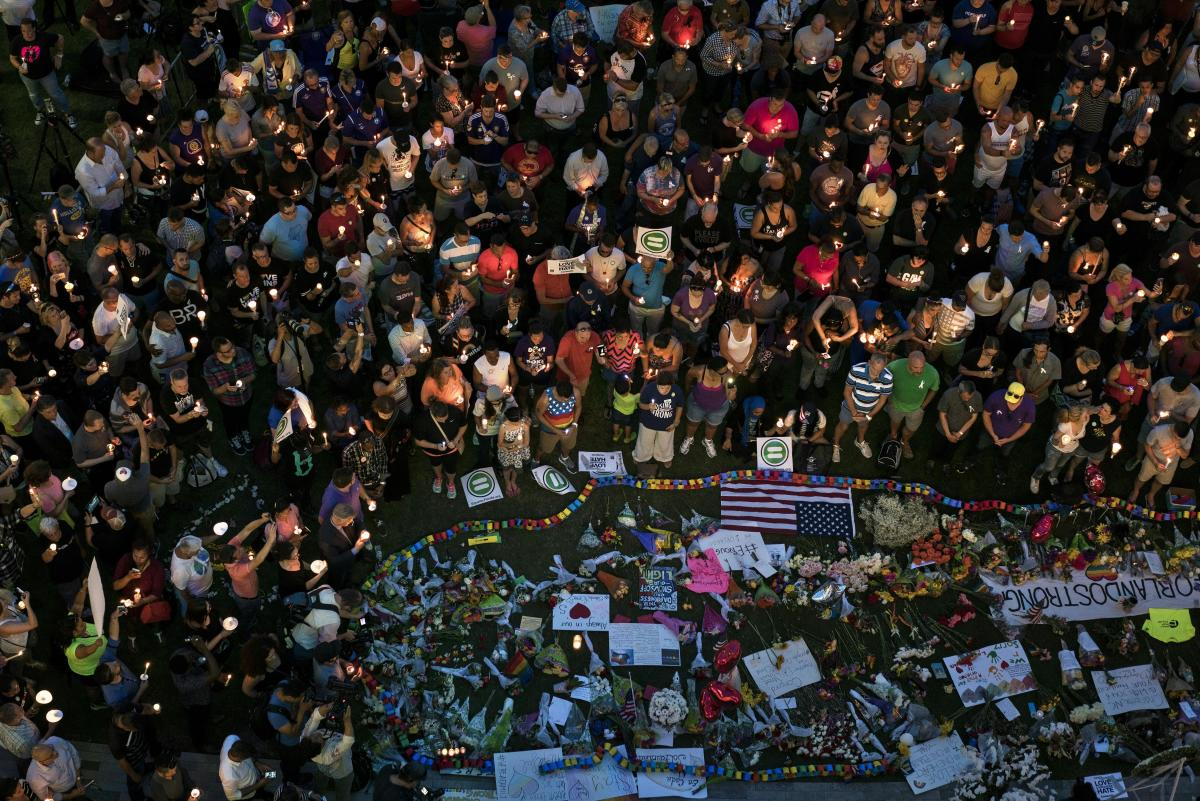 Mourners hold candles while observing a moment of silence during a vigil for the mass shooting victims at the Pulse nightclub in Orlando, Florida on June 13, 2016 .