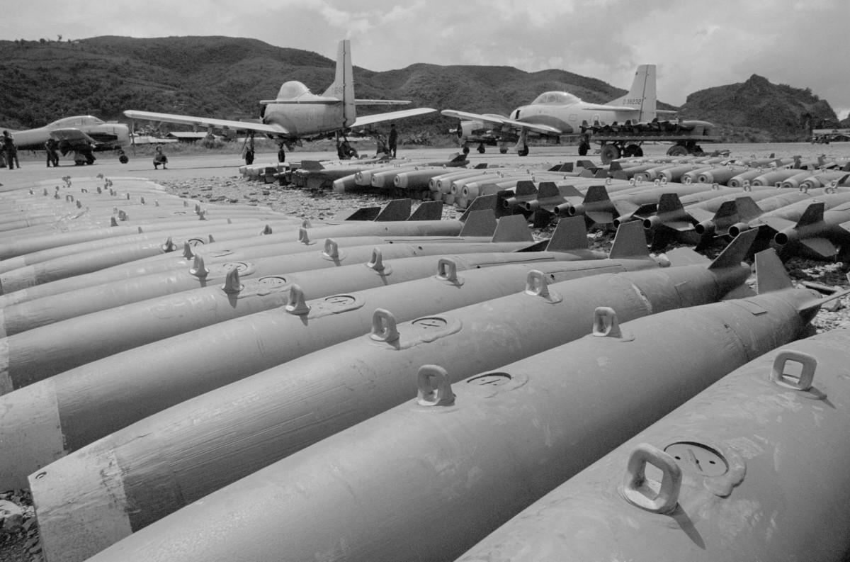 "The CIA-sponsored ""Secret Army"" of Major Gen. Vang Pao at Long Cheng, where the U. S. and Laotian governments permitted newsmen a rare glimpse of the base in 1972. A converted T-28 trainer aircraft is seen near 250-pound bombs used by Meo pilots of Vang Pao's ""mini-Air Force"" against North Vietnamese in northern Laos."
