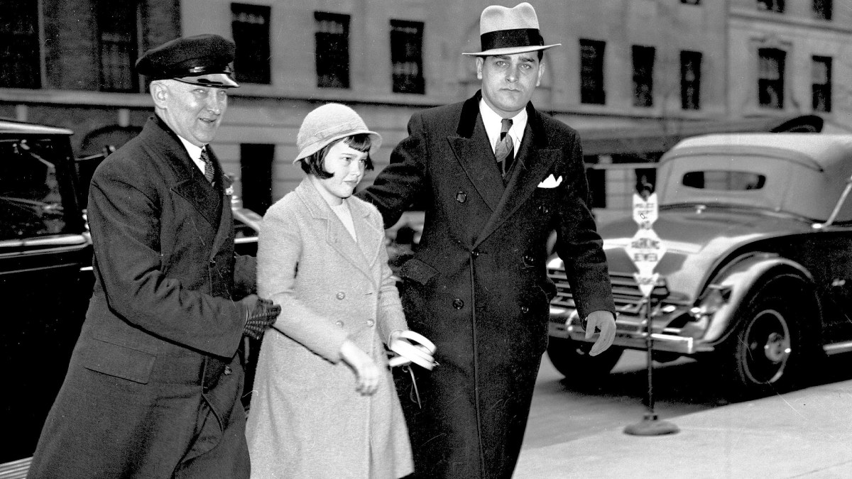 Assisted by her chauffeur, Gloria Vanderbilt is seen returning to her mother's home during the custody battle, circa 1935.