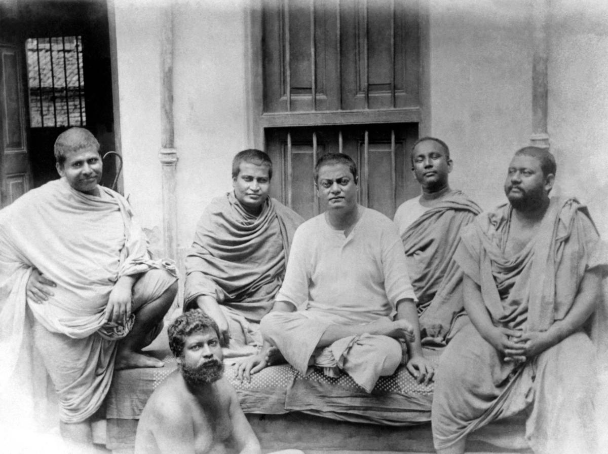 Vivekananda sitting center among a group of men.