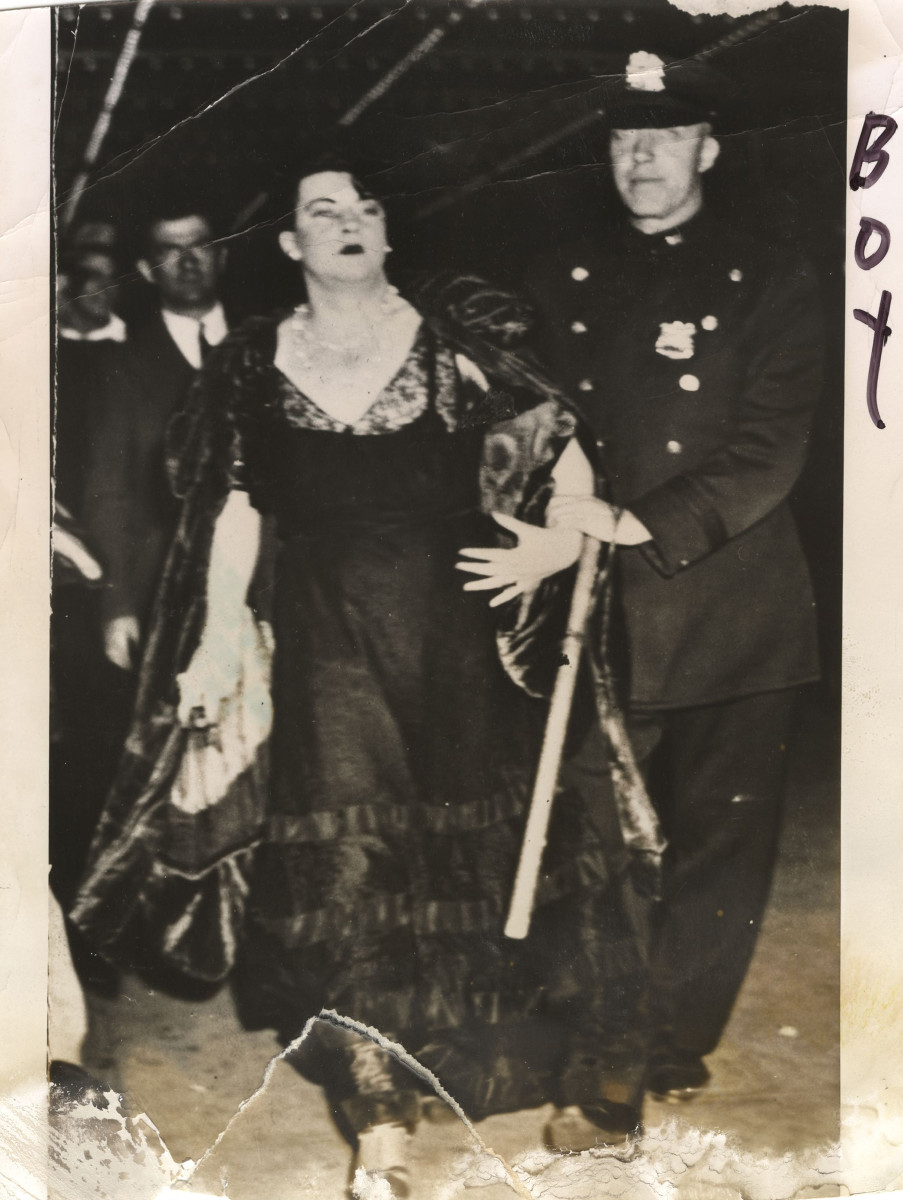 A police officer arrests a male cross-dresser in a ball gown, circa 1940.
