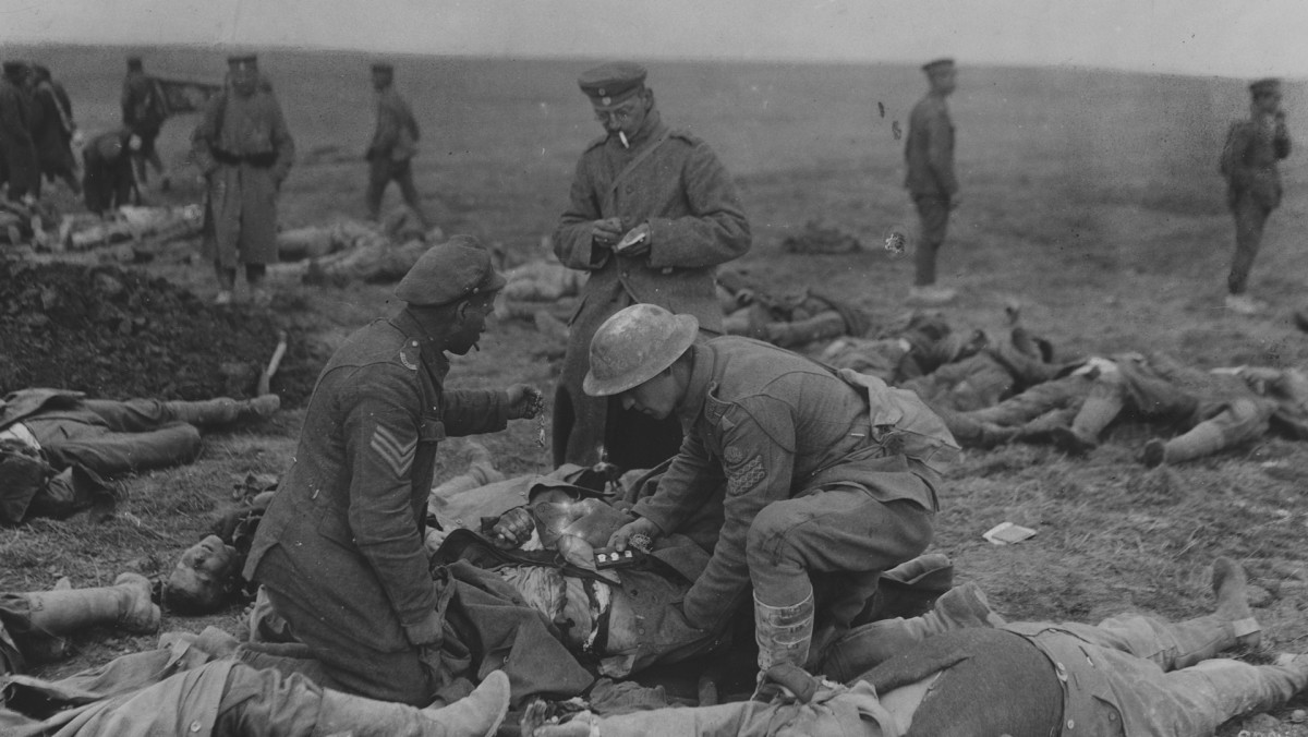 A German soldier forces British prisoners to pilfer corpses of fallen soldiers.