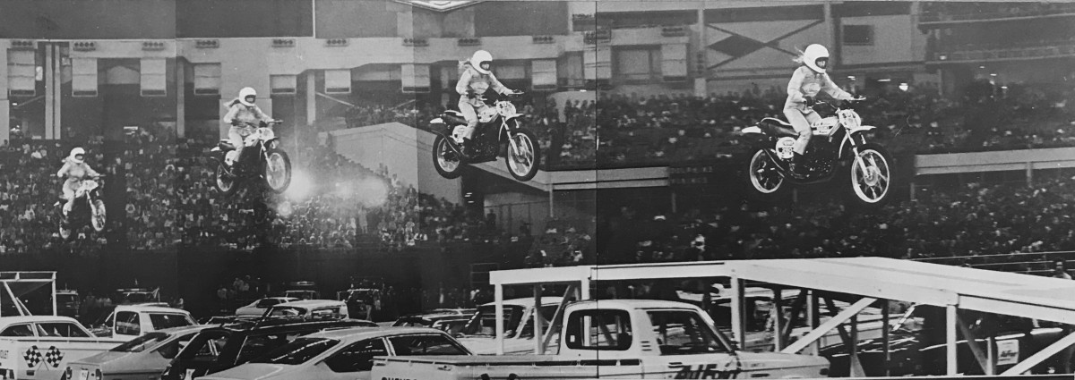 Stop-action photo of stunt motorcyclist Debbie Lawler in mid-air jumping over 16 pickup trucks