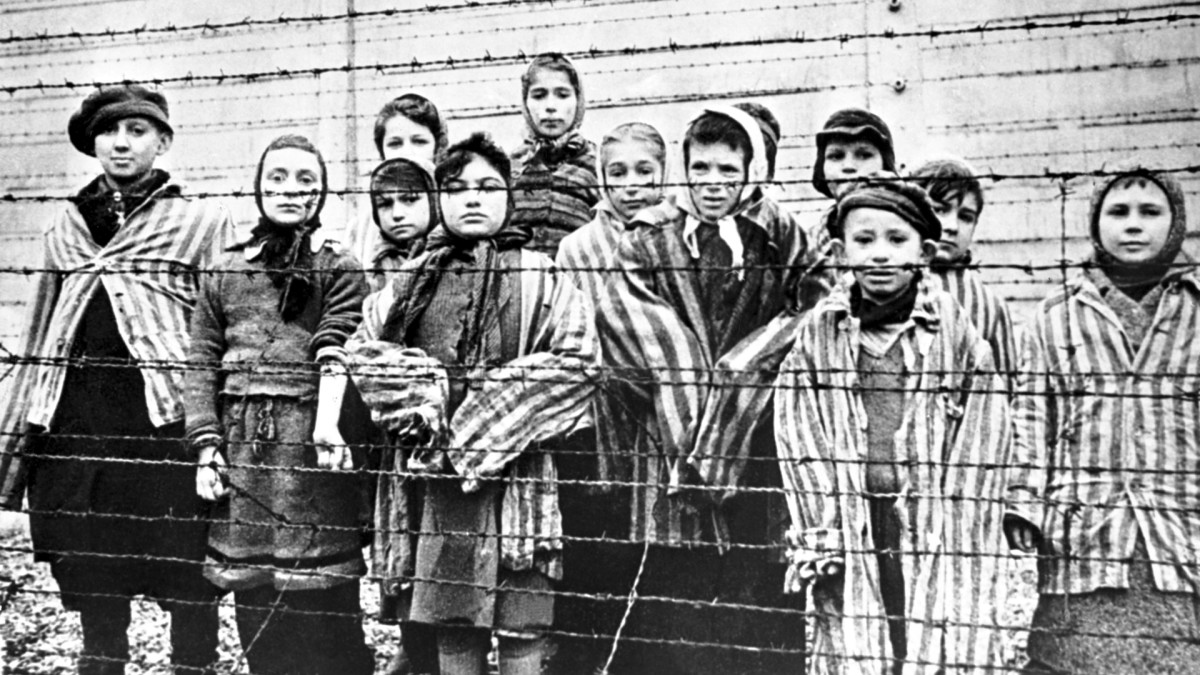 A group of child survivors behind a barbed wire fence at Auschwitz-Birkenau, on the day of the camp's liberation on January 27, 1945. Twins Eva and Miriam Mozes are pictured on the far right.