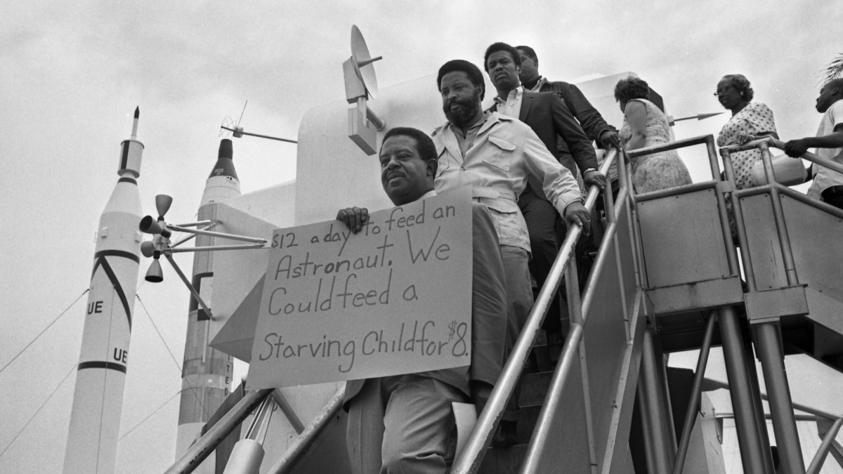 Reverend Ralph Abernathy, flanked by associate Hosea Williams stand on steps of a mockup of the lunar module displaying a protest sign while demonstrating at the Apollo 11 moon launch site.