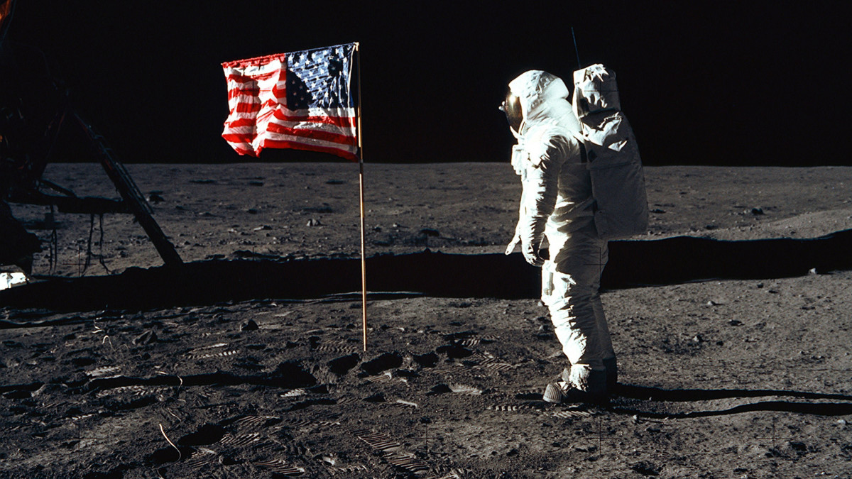 Astronaut Buzz Aldrin stands next to the American flag as one of the first men on the moon, 1969.