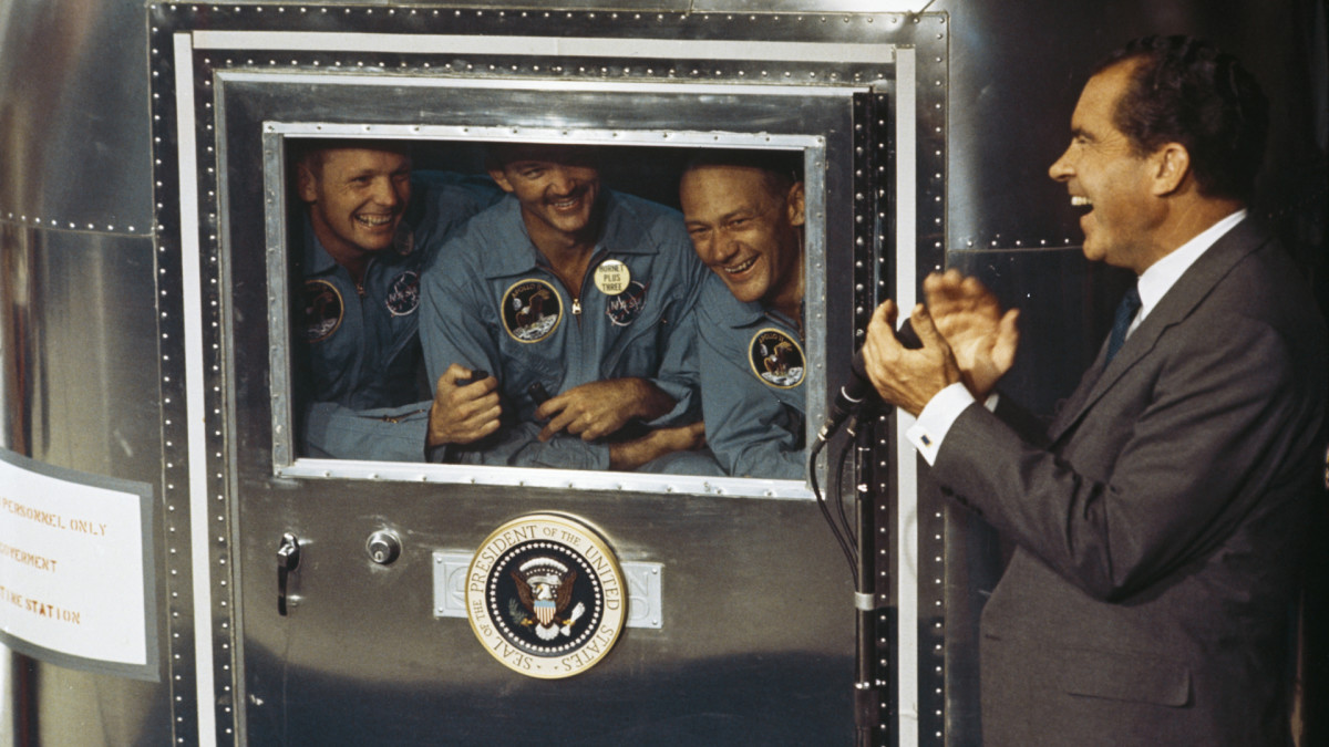 resident Richard Nixon speaking with Apollo 11 crew members Neil Armstrong, Michael Collins and Buzz Aldrin who were subjected to a period of quarantine upon their return to Earth.