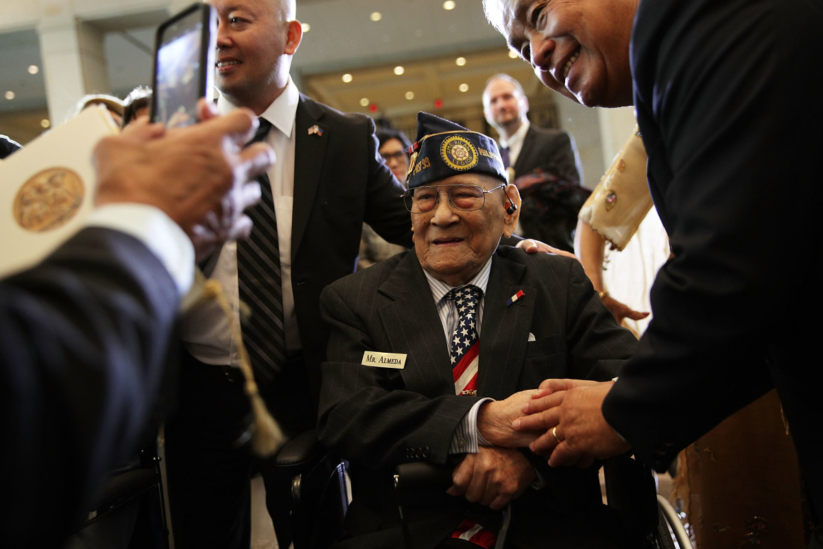 Celestino Almeda, a Filipino veteran representing the Philippine Commonwealth Army, is greeted by other guests during a Congressional Gold Medal presentation ceremony October 25, 2017.
