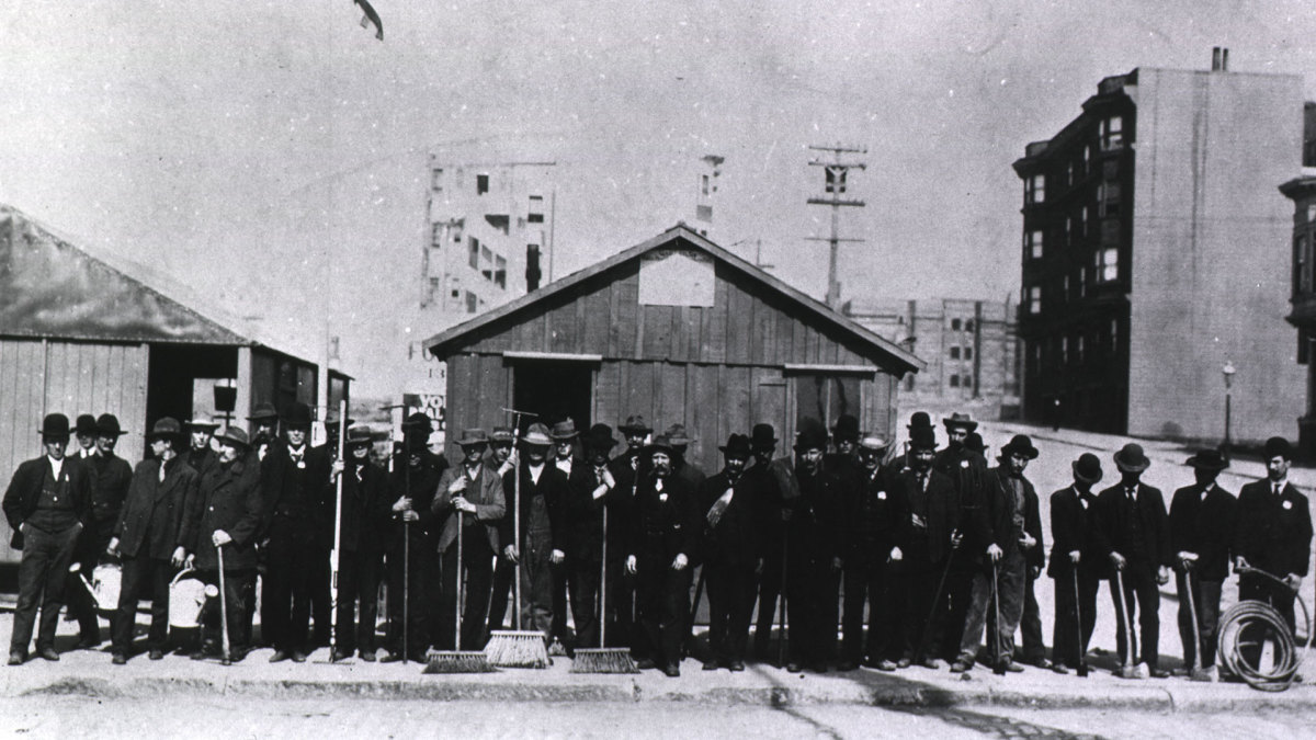 Group portrait of health workers with brooms, sprinkling cans, axes, hoses, rakes, shovels and other equipment used to destroy rat habitation areas, standing in front of the storeroom (on left) and U.S. Public Health Marine Hospital Service District Headquarters during the San Francisco plague campaign.