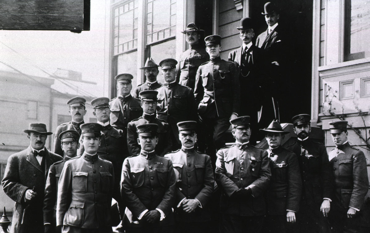 Group portrait of P.A. Surgeon Rupert Blue (first row, fourth from right), members of his staff, and three men in civilian clothes, standing in front of the San Francisco Plague Suppressive Headquarters at Filmore & Page Sts. in San Francisco, California during the San Francisco plague campaign.