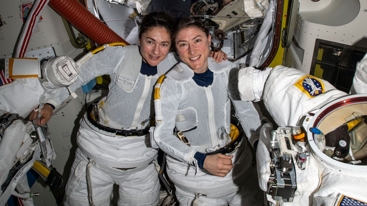 NASA astronauts Jessica Meir and Christina Koch put on their spacesuits as they prepare to leave the hatch of the space station.