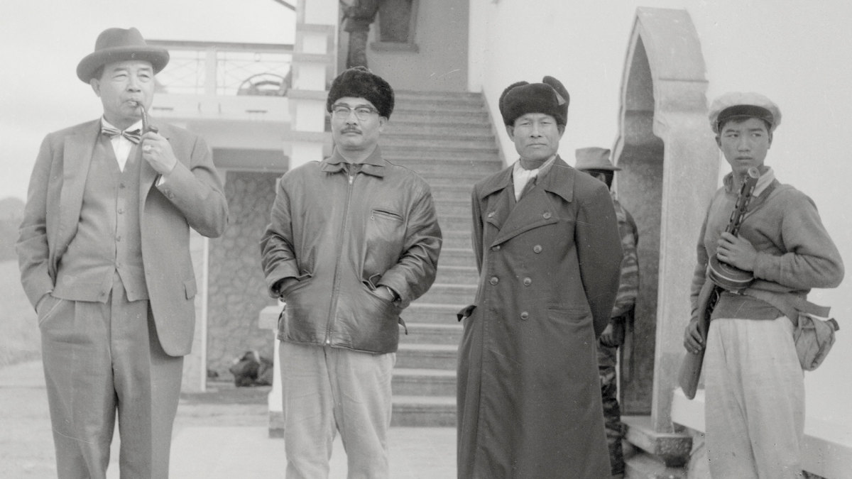 An armed guard (far right) standing next to (L-R) Souvanna Phouma, Neutralist Premier of the Laotian Coalition Government, his pro-communist, half-brother, Souphanouvong, and General Singkapo, commander-in chief of the Pathet Lao Army, 1963.