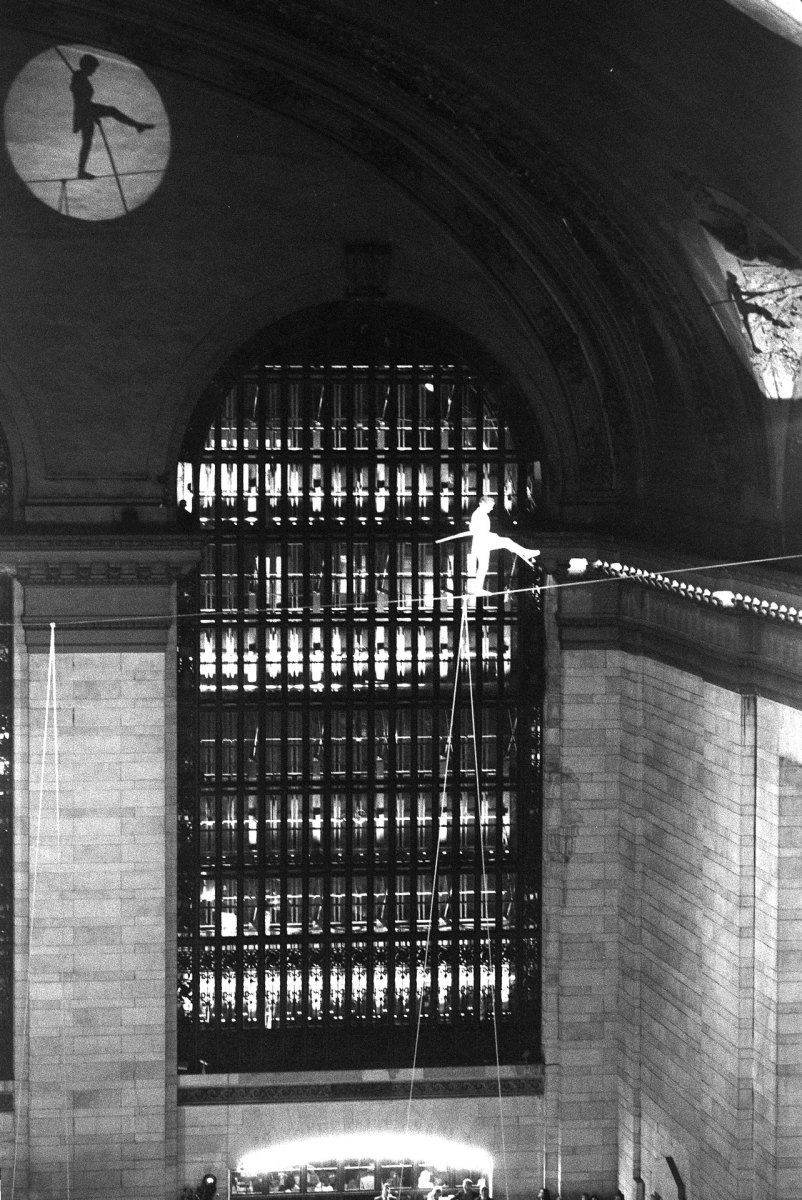 High wire artist Philippe Petit performing above a crowd at Grand Central Terminal in 1987.