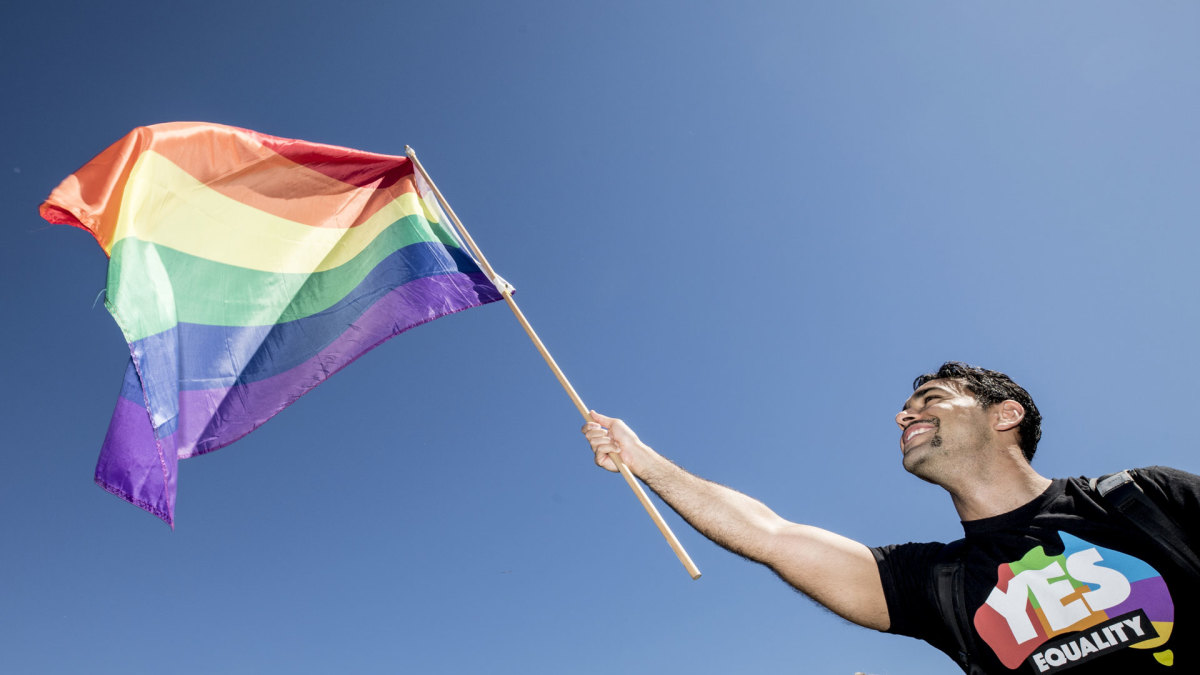A man waves a rainbow flag on November 15, 2017 in Sydney, Australia as Australians were asked to vote in the Marriage Law Postal Survey regarding sam-sex marriage.