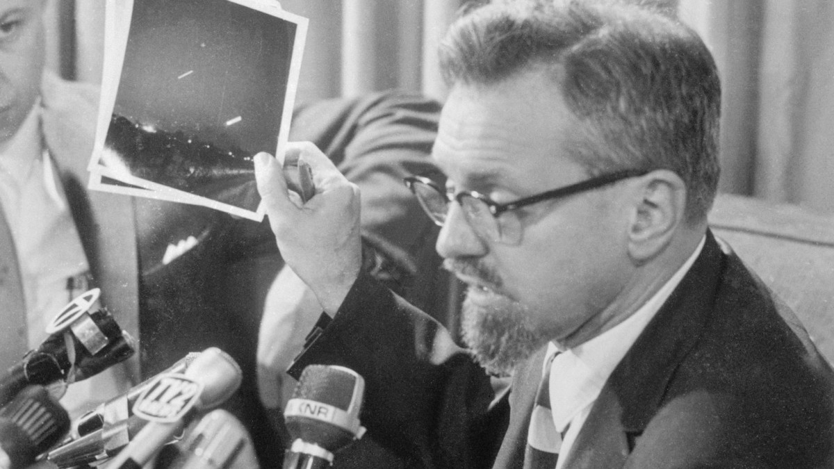 Dr. J. Allen Hynek, telling newsmen at a press conference that the photograph he is holding, widely circulated in the news media as a UFO spotted in Michigan, is a time exposure of the crescent moon and the planet Venus.