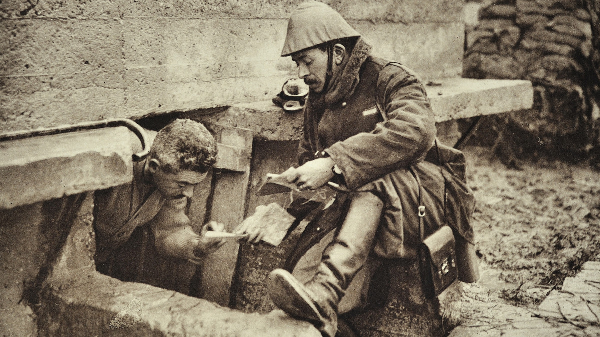 A soldier emerges from a trench to receive a letter in Flanders during World War I in Belgium.
