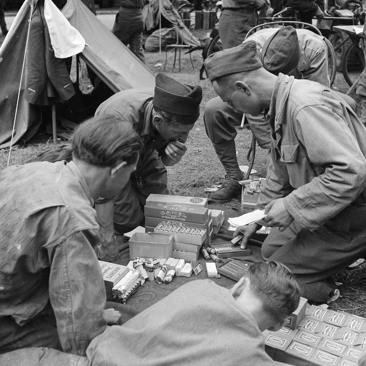 Soldiers unpacking boxes of tobacco, chewing-gum, chocolate, tooth powder and other rations.
