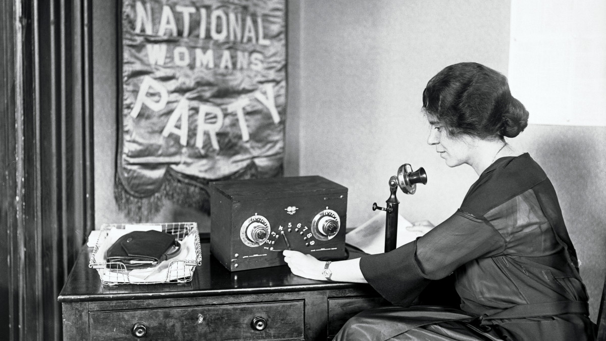 Alice Paul, suffragist and vice president of the National Women's party broadcasts plans for the dedication of the New National Headquarters at Washington from her desk at the Capitol. She began the first version of the Equal Rights Amendment in 1923.