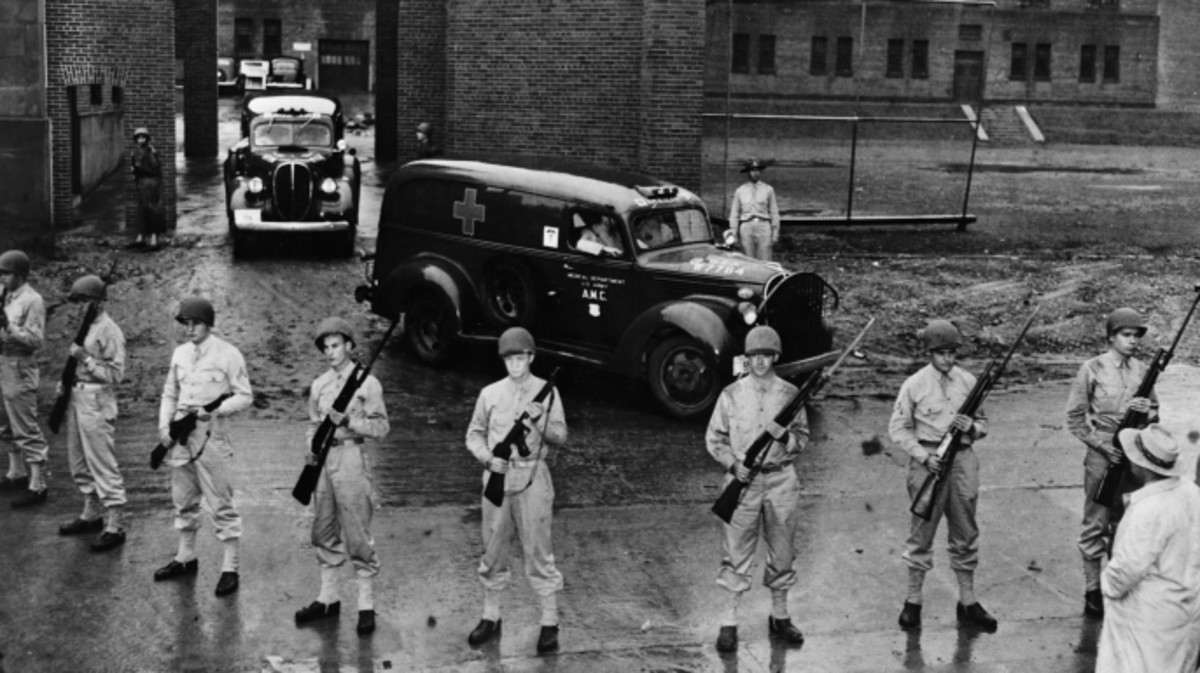 Armed soldiers guard the ambulances carrying the bodies of six executed Nazi saboteurs.