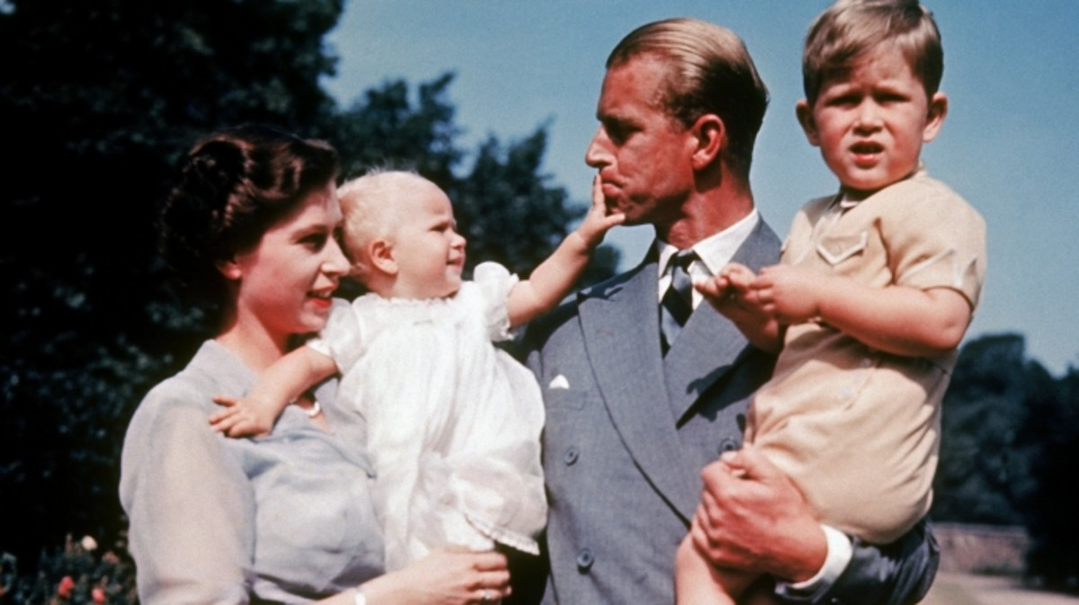 Queen Elizabeth II holding daughter Anne and Prince Philip holding son Charles.