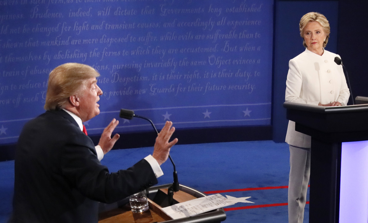 Republican nominee Donald Trump gestures as Democratic nominee Hillary Clinton looks on during the final presidential debate in Las Vegas, Nevada on October 19, 2016.