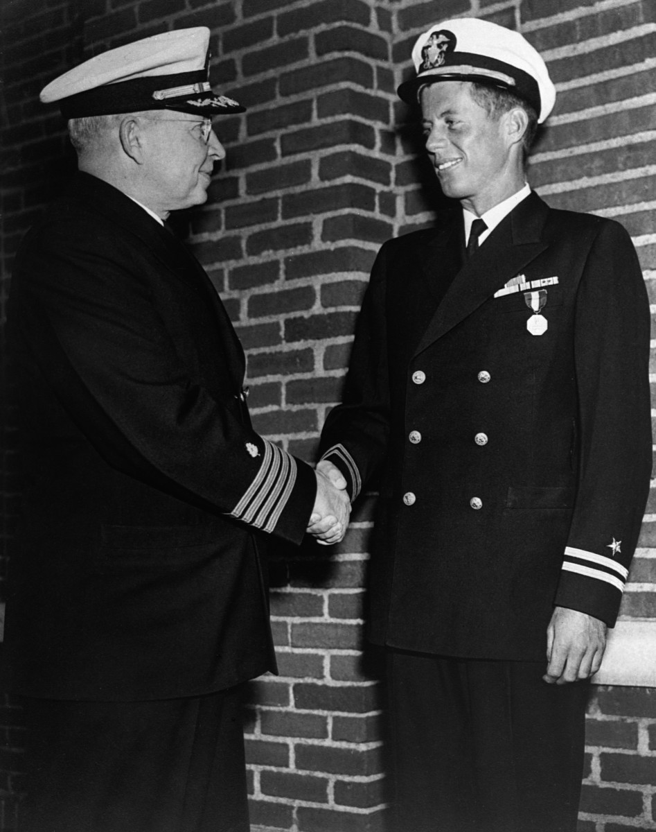 John F. Kennedy shakes hands with Captain Conklin after being presented with a medal for heroism in service in the Navy during WWII.