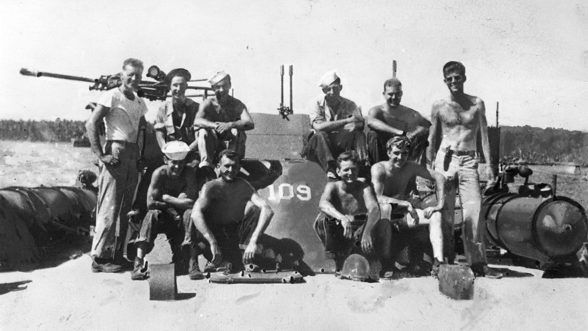John F. Kennedy and crewmen of the PT-109. Back Row (L-R) Allan Webb, Leon Drawdy, Edgar Mauer, Edmund Drewitch, John Maguire, John F. Kennedy (standing, far right). Front Row (L-R) Charles Harris, Maurice Kowal, Andrew Kirksey, and Lenny Thom.