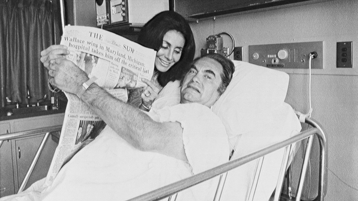 George Wallace and his wife Cornelia, holding up a newspaper indicating his victories in the May 16 Maryland and Michigan Democratic Presidential primaries, now paralyzed from the waist down by one one of four gunshot wounds suffered while campaigning..