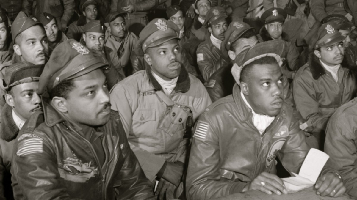 "Tuskegee airmen attending a briefing in Italy in 1945. First row (l-r): Hiram E. Man, unidentified airman, Newman C. Golden, Bertram W. Wilson Jr., Samuel W. Watts Jr., Second row (l-R): Armour G. McDemoe, Howard C. Gamble, Harry T. Steward, Jr, Earle R. Lane, Wickliffe, Wyrain T. Shell, Harold M. Morris, John E. Edwards, John H. Porter, James H. Fischer, Wyrain T. Shell. Third row (l-r): William E. ""Porky"" Rice, Tony Weaver, Charles L. White, George Arnold Lynch, Samuel L. Washington, Calvin J. Spann, Frank N. Wright."
