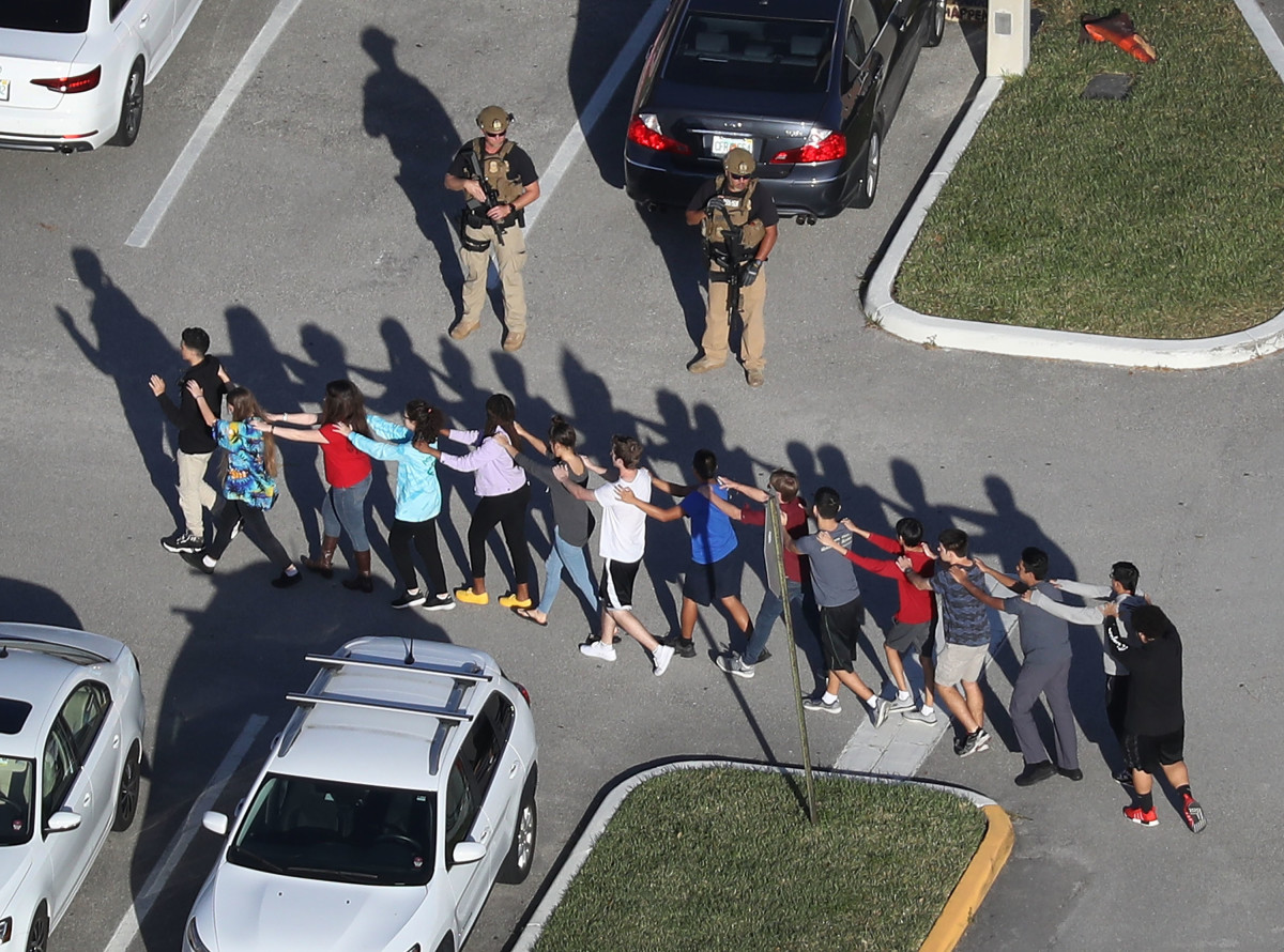 Students walking out of the Marjory Stoneman Douglas High School in Parkland, Florida after a shooter killed and injured multiple people there on February 14, 2018.