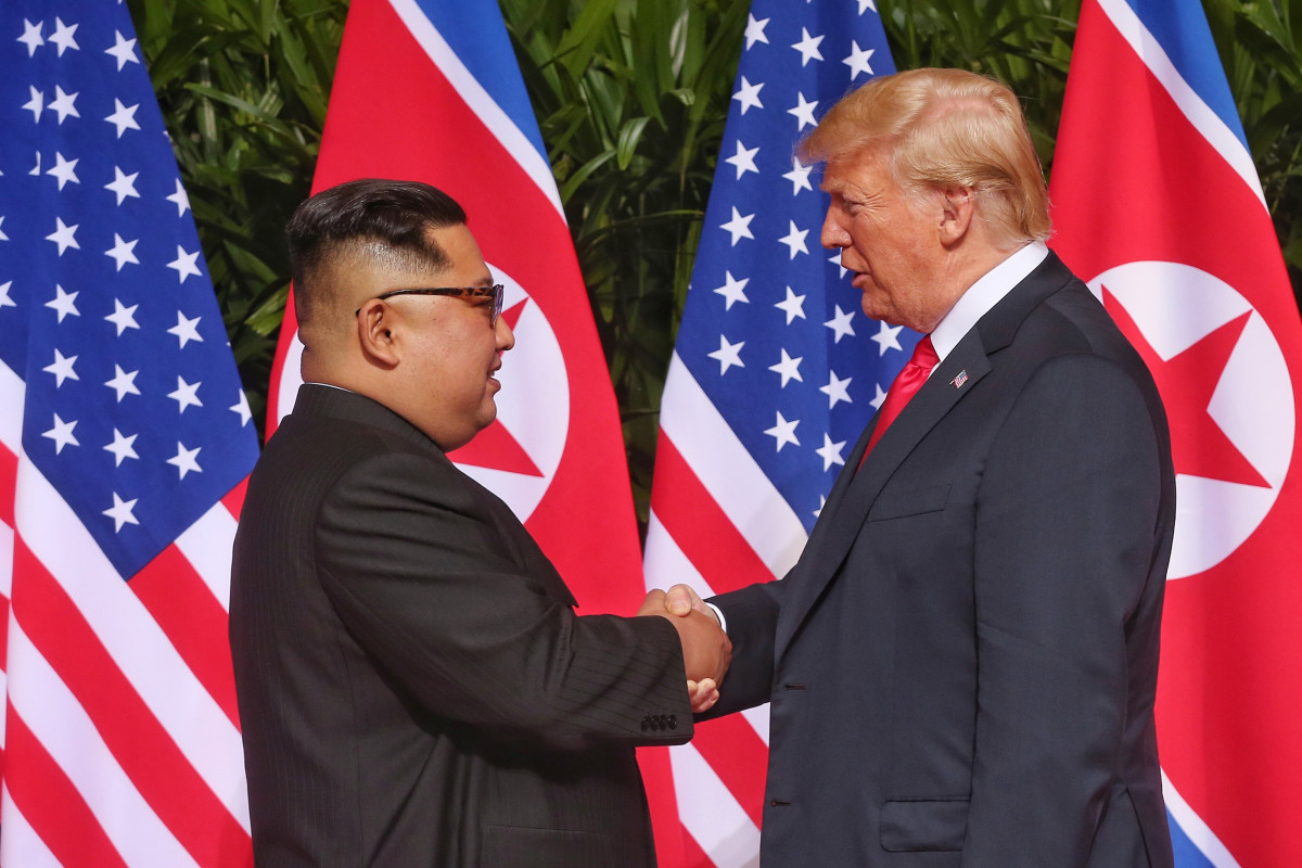 North Korean leader Kim Jong-un (L) shakes hands with U.S. President Donald Trump during their historic summit on June 12, 2018 in Singapore.