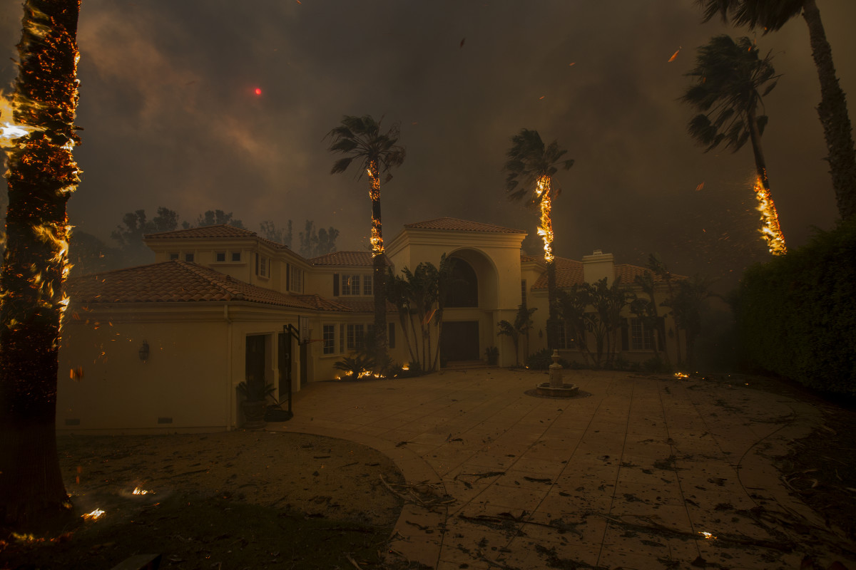 Embers fall from burning palms and the sun is obscured by smoke as flames close in on a house at the Woolsey Fire on November 9, 2018 in Malibu, California.