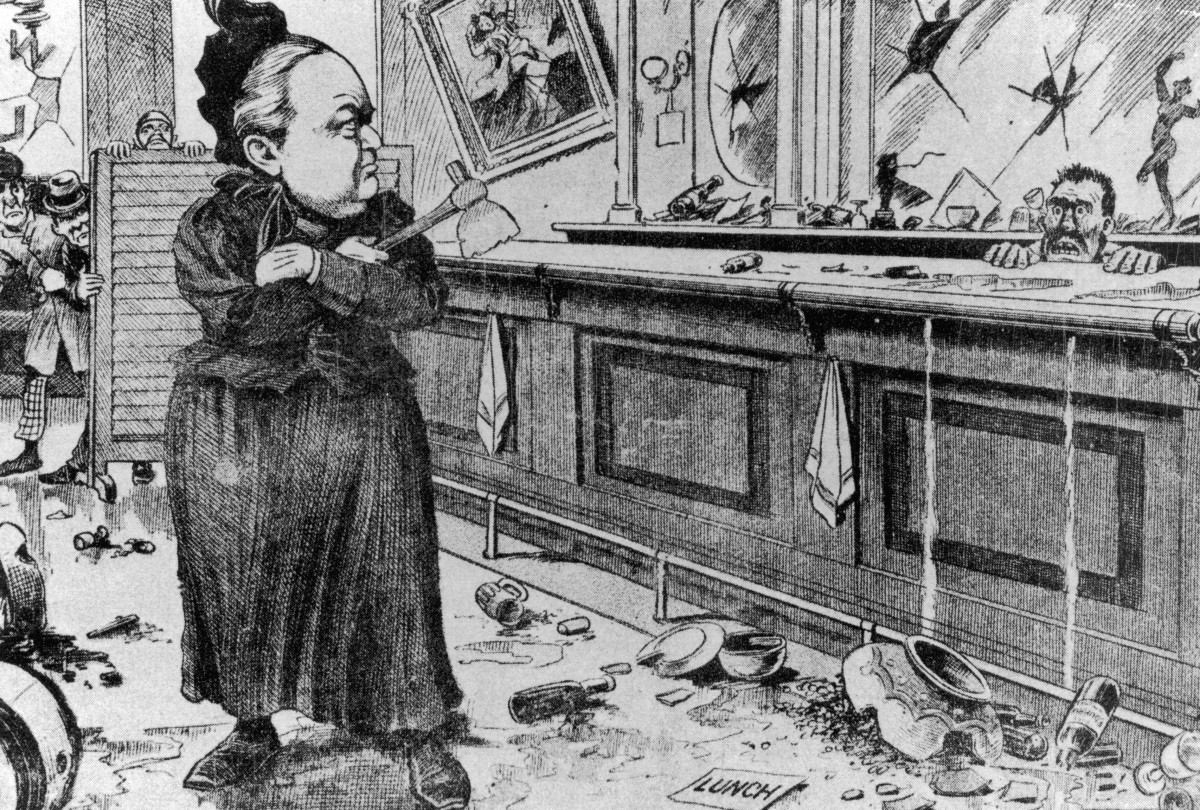 An editorial cartoon circa 1895 depicting American temperance activist Carry Nation glaring at a terrified bartender as she holds a hatchet in a saloon.