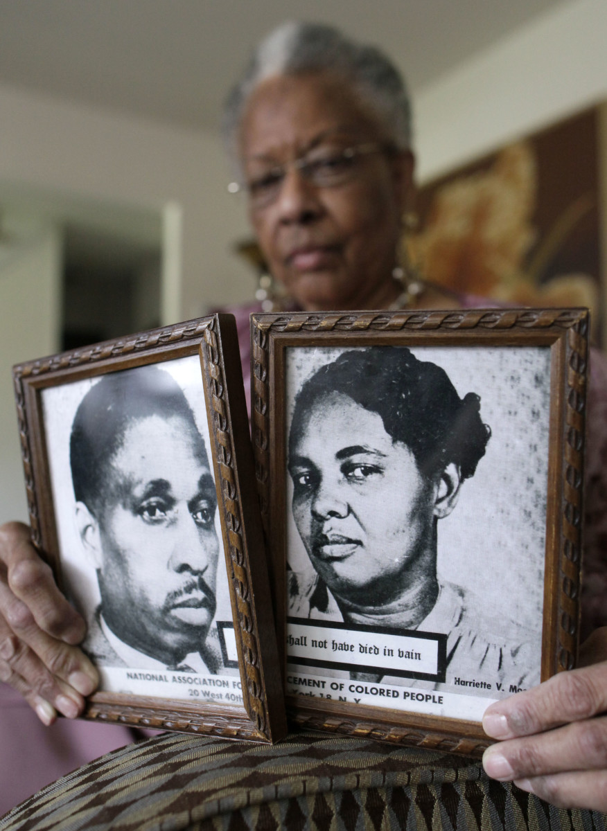 Juanita Evangeline Moore holding photos of her parents, Harry and Harriette Moore, at her home in 2011. No one was charged for the crime.