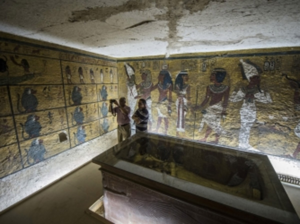 Egyptian archaeologists take pictures next to the sarcophagus of King Tutankhamen in his burial chamber.