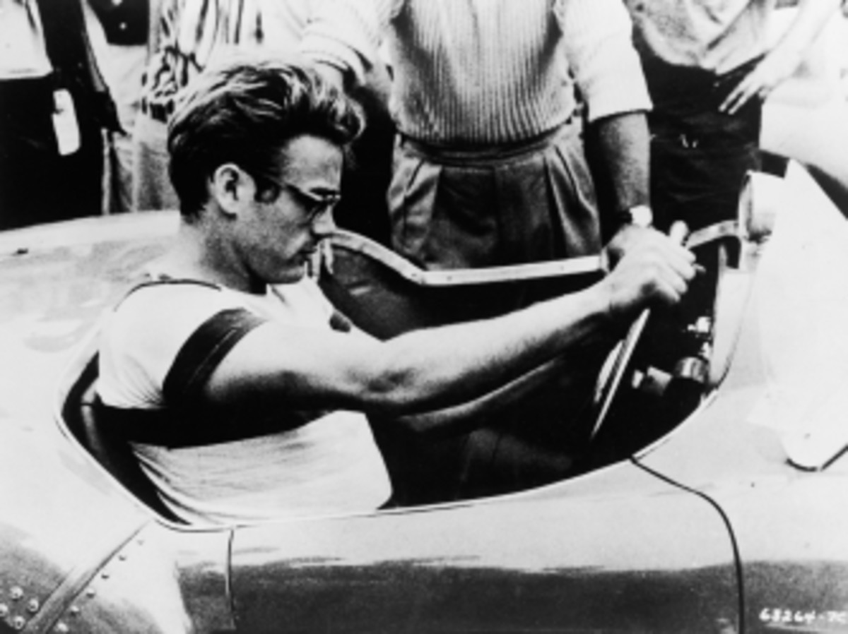 James Dean sits behind the wheel of a sports car in a still from 'The James Dean Story,' 1957.
