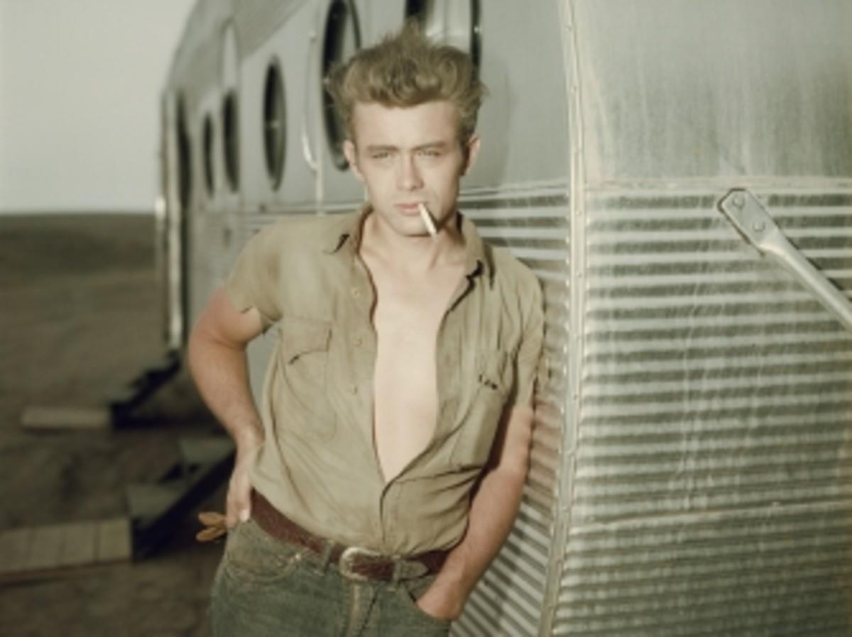 James Dean leaning against a dressing room trailer on the set of director George Stevens's film, 'Giant,' in 1955.