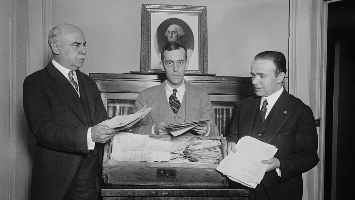A trunk belonging to George Washington's only sister, Betty, containing upward of 2,000 original papers of George Washington's family and contemporaries that was brought to Washington by Henry Woodhouse. He is seen inspecting papers with William Tyler Page, Clerk of the House of Representatives and William Selden Washington, descendant of George Washington's brother.