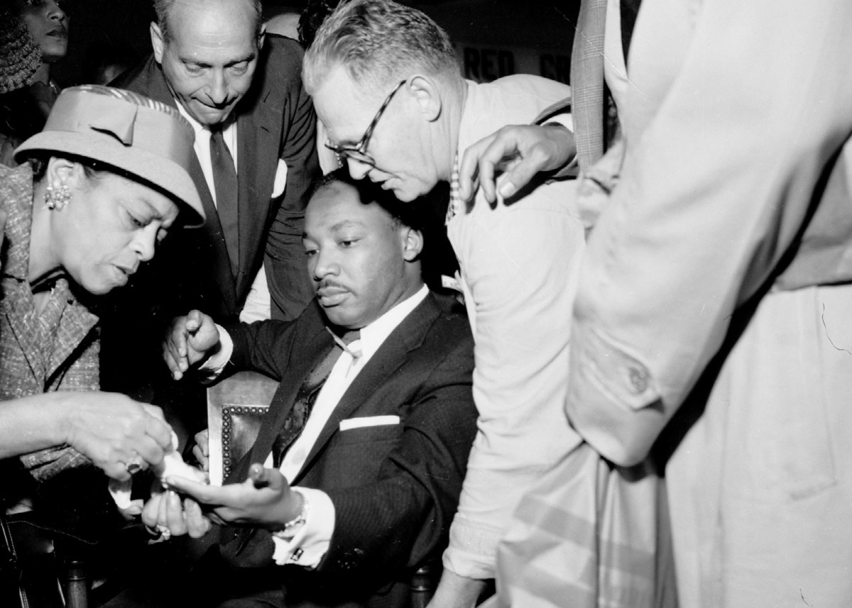 A letter opener protruding from his chest, Martin Luther King, Jr. is shown having another wound treated at W. 123rd St. police station in Harlem after being stabbed at a book signing in 1958.