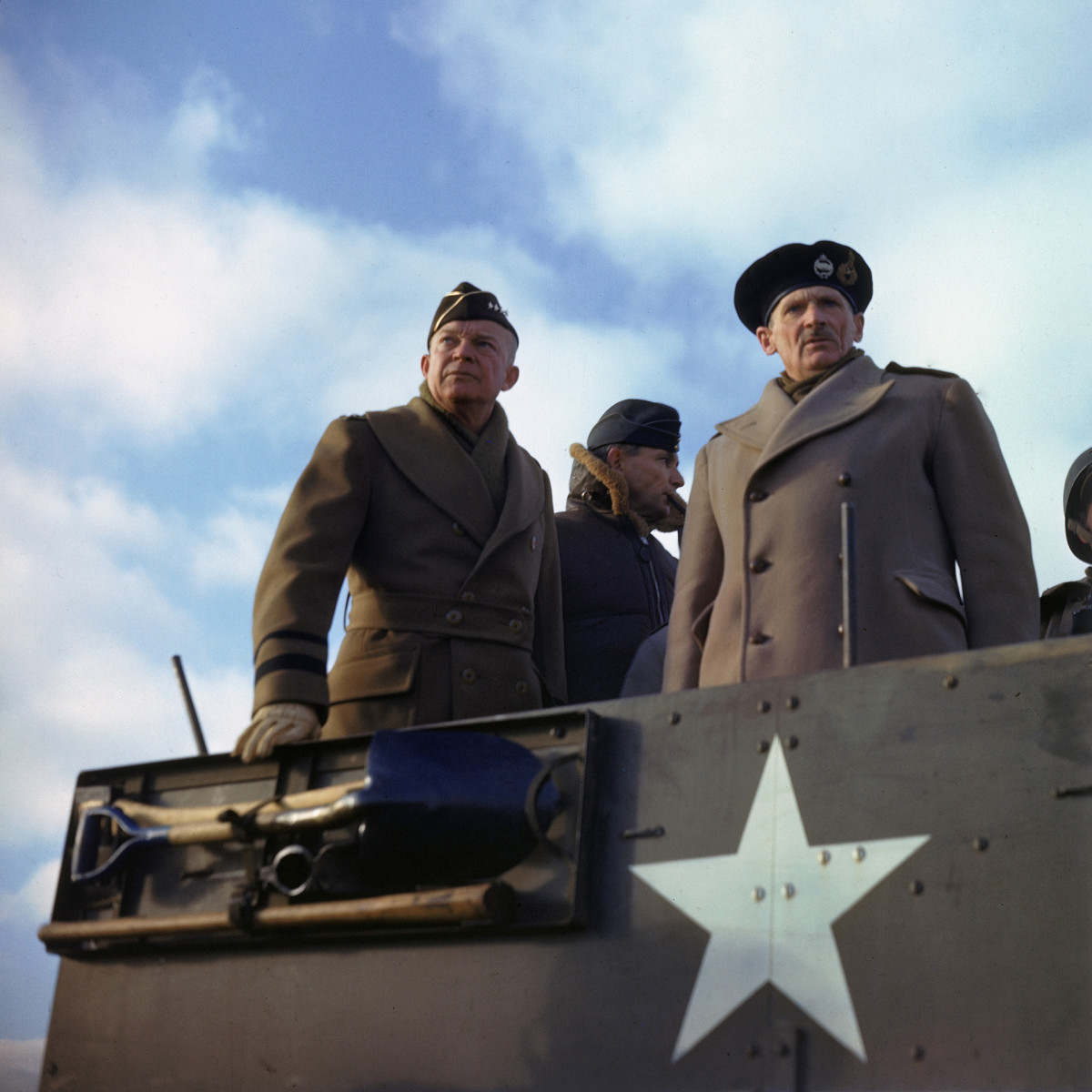 General Dwight D. Eisenhower, with his deputy, British Chief Air Marshal Arthur Tedder, and the principal commander of Allied ground forces in Europe, British General Bernard L. Montgomery in a US armored vehicle as they review a tank exercise in England, 1944.