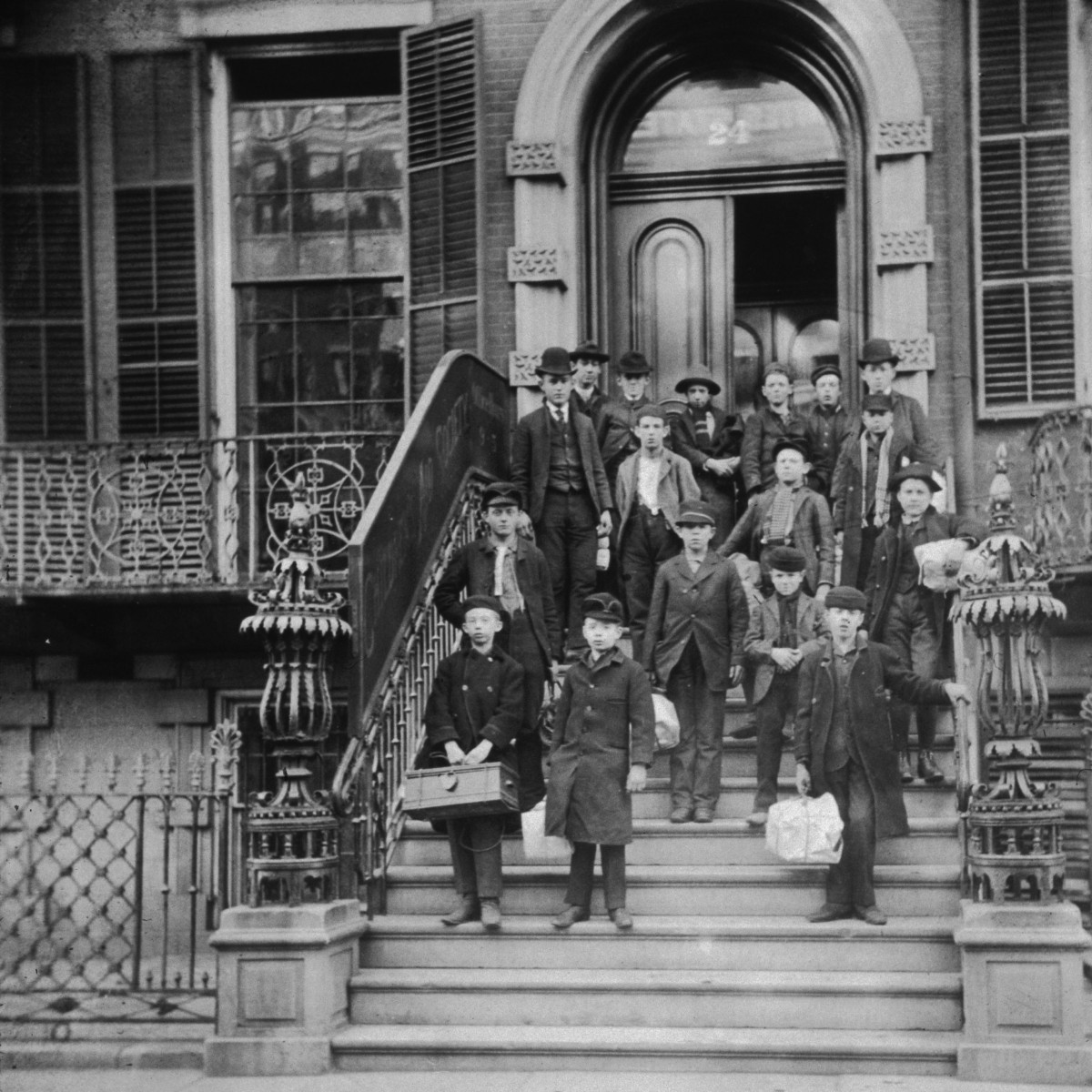 A group outside of the Children's Aid Society's central office in New York City, circa 1895. The children hold satchels with their belongings as they prepare to travel west.