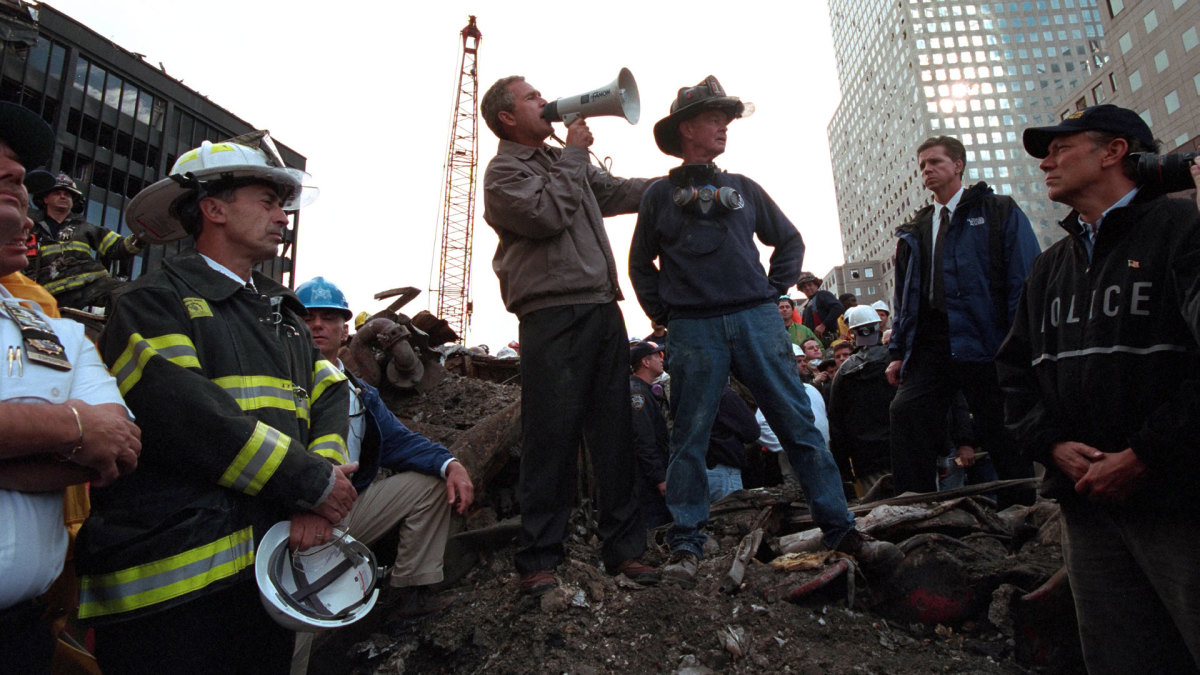 Standing atop rubble with retired New York City firefighter Bob Beckwith, President George W Bush rallies firefighters and rescue workers at the site of the collapsed World Trade Center in New York City, September 14, 2001.