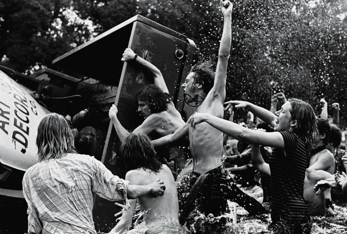 Young demonstrators shout and cheer as they overturn a truck trailer in the Reflecting Pool on the Mall facing the Washington Monument.