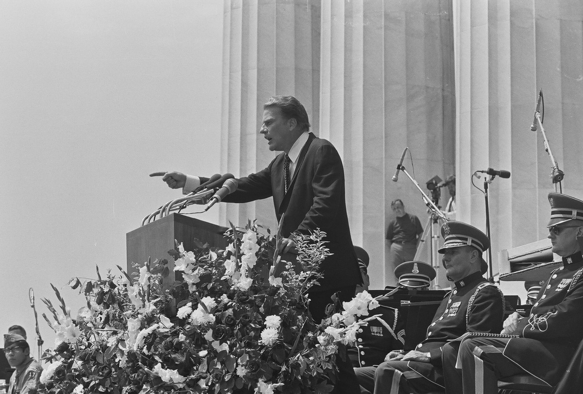 American evangelist Billy Graham speaks from a podium on the steps of the Lincoln Memorial while surrounded by uniformed members of the armed forces duting 'Honor America Day,'  in Washington, DC on July 4, 1970.