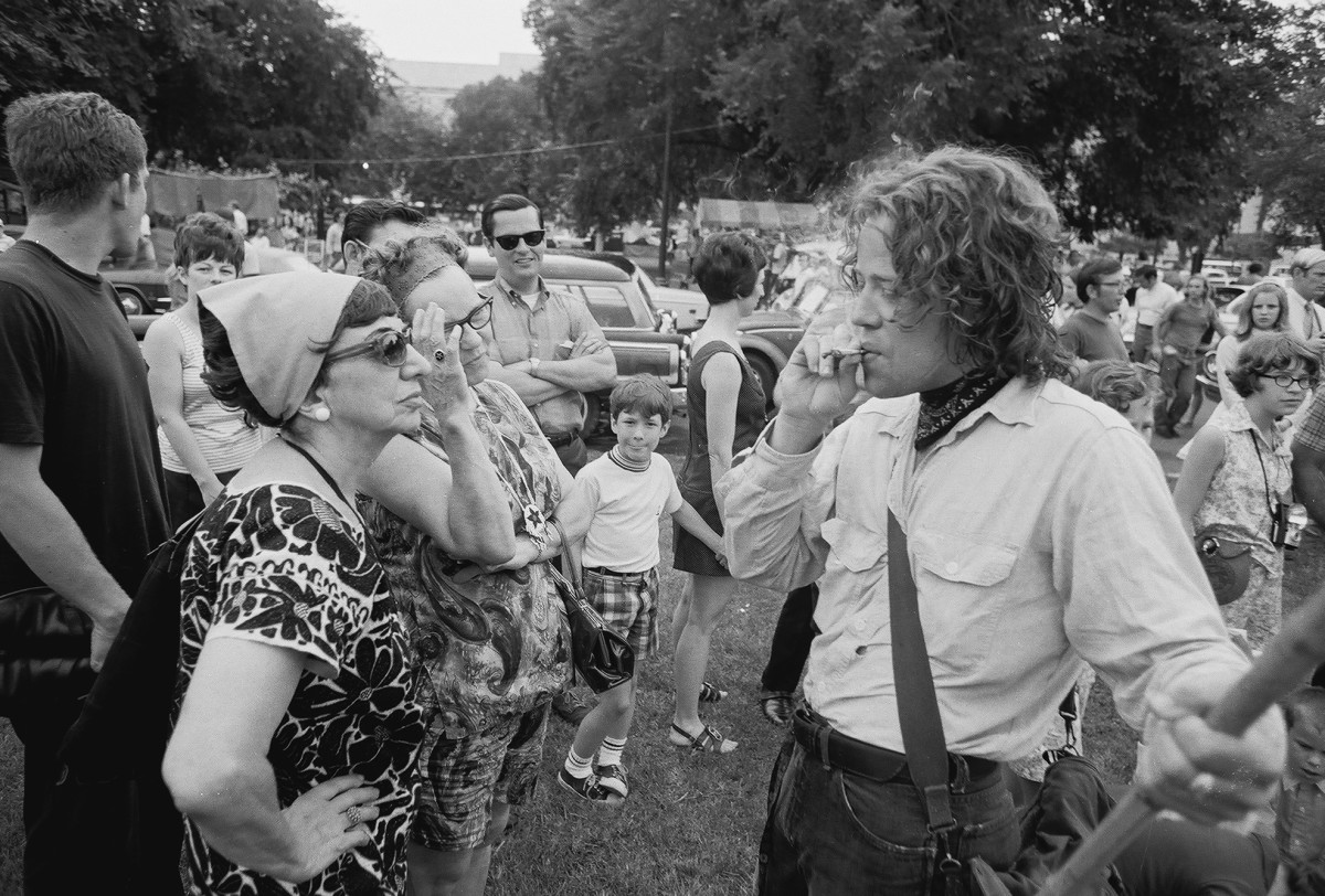 An unidentified young man smokes marijuana for the benefit of a pair of middle-aged women, along with several other onlookers, during the 'Honor America Day Smoke-In' thrown by marijuana activists to protest the official 'Honor America Day' ceremonies.
