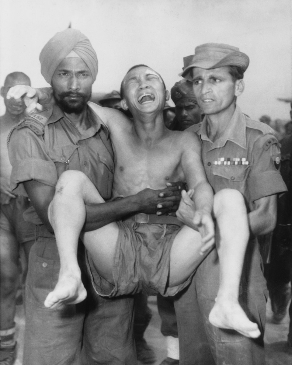 Two Indian soldiers carrying a weeping Chinese POW to the exchange point in Panmunjom, North Korea, for return to the Communists after the Korean War in the early fall of 1953. He was among 65 Chinese soldiers who asked to be repatriated to their homeland.