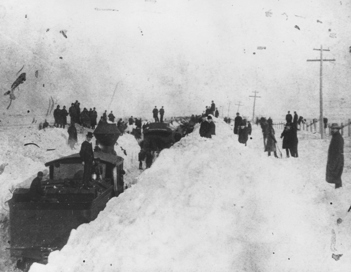 View of several people and a train stopped on snow-covered tracks after the great blizzard of 1886. This photograph was taken in Ford County, Kansas.