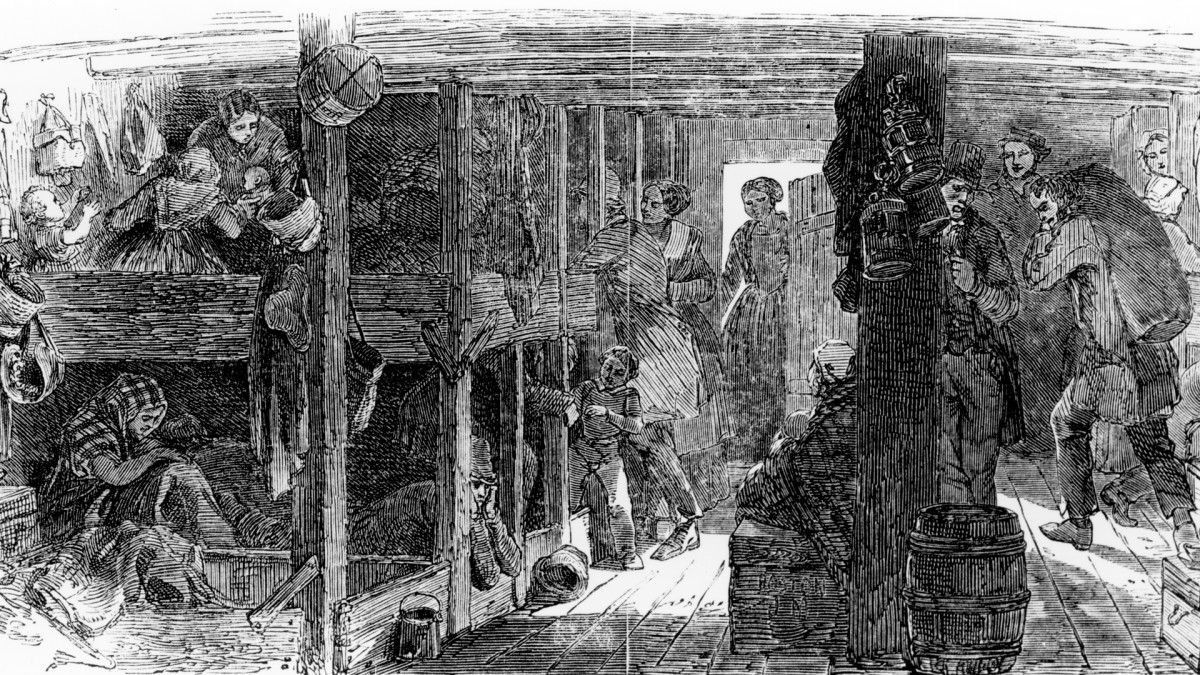 Men, women and children in bunks between decks on board an immigrant ship in the mid 19th century.