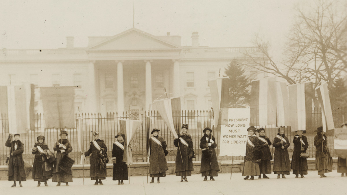 "Suffragists on picket line in front of the White House, circa 1917. One banner reads: ""Mr. President How Long Must Women Wait For Liberty""."