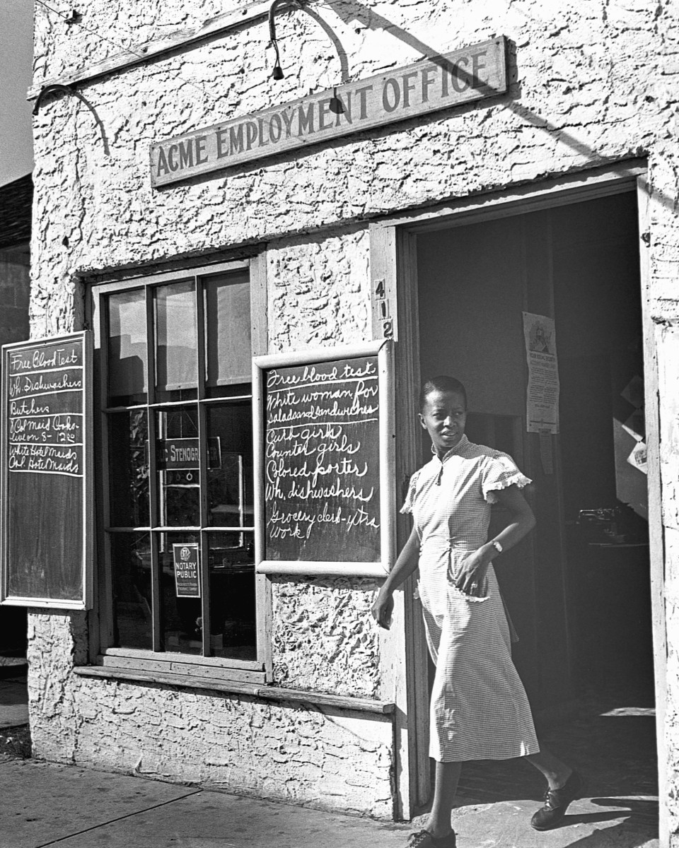 A woman walking out of an employment agency in Miami, Florida, circa the 1930s.